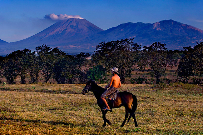 The San Cristobal Volcano, the largest in Nicaragua, emits steam under a Nicaraguan cowboy and his horse.
