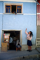 A girl tosses a package to her brother in the window of their home in Quispe, Bolivia.