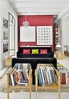 A contemporary living room with barrel ceiling. The room is white with vibrant accent colours. A black sofa provides a strong colour contrast against a pink wall. Two simple wooden armchairs become a novel place to display books.