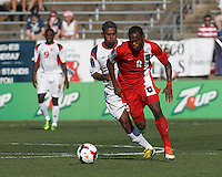 Belize forward Deon McCaulay (9) on the attack as Cuban midfielder Jaime Valencia (8) closes. In CONCACAF Gold Cup Group Stage, the national team of Cuba (white) defeated national team of Belize (red), 4-0, at Rentschler Field, East Hartford, CT on July 16, 2013.