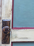 An old door is painted blue, white and red.