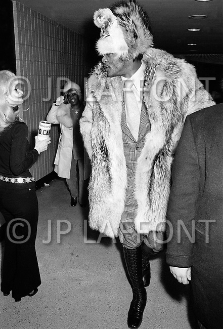 Manhattan, New York City, NY - March 8, 1971  <br /> Muhammad Ali and Joe Frazier at Madison Square Garden.<br /> Billed as the &lsquo;Fight of the Century&rsquo; African-American boxing fans and dandies attended wearing the most glam-fashions of the day. Furs, minis and thigh-high platform boots were all the rage.