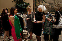 """Newport, California, July 22, 2011 - Jill Alexander (second from right) shows a green jacket to customers at The Divorcee Sale at the Pelican Hill Resort in Orange County. Organized by Jill Alexander, the sale offers luxury items most of which from uber-rich divorcees looking to unload their proverbial baggage. The event also donates 25 percent of its profits to breast cancer research...Alexander, who has actually never been married, started The Divorcee Sale this past spring after noticing a trend amongst her friends and colleagues going through divorces. """"Many women have an attachment to these things and they just want to move on,"""" says Alexander. She added that the consignment shops were full and not really offering much in the way of sympathy in the situation. Alexander is different in that she visits the home of the divorcees, often with cakes and tissues, and acts as both a consignor and a confidant. ."""