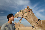 A male tourist gets a kiss from a camel at the Pyramids of Giza near Cairo, Egypt.