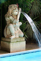 A limestone water feature in the form of a Hindu god at one end of the outdoor swimming pool