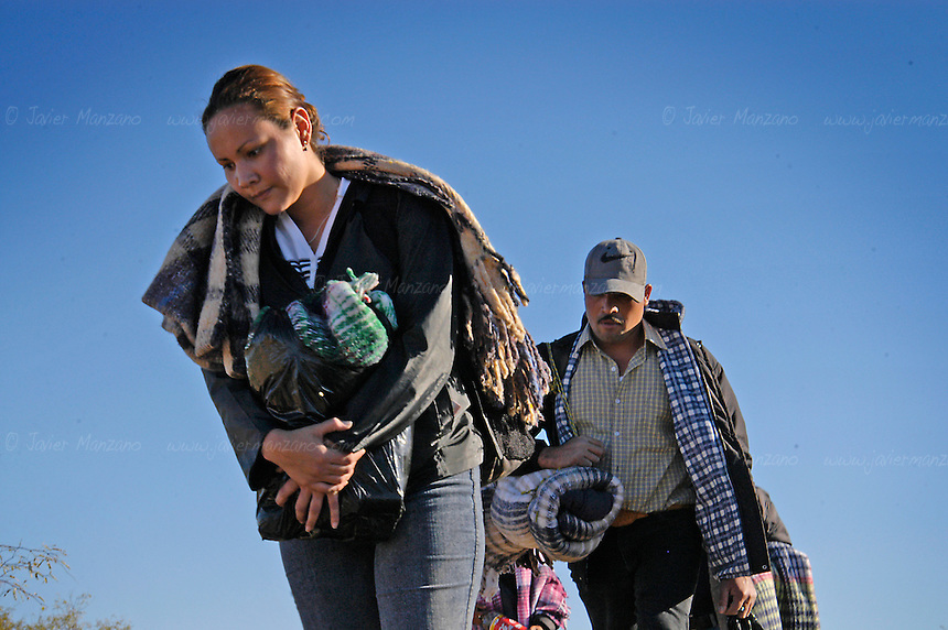 """A large group of Immigrants, guided by two """"coyotes"""" or guides,  walk on the desert of Sonora bound for the border with Arizona. This group consisted of 37 border crossers, from four different countries- They included people from Mexico, Honduras, El Salvador and one Brazilian. .Sasabe, Mexico.  01/23/05"""