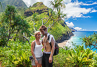 A couple pauses on the Kalalau Trail on their way to Hanakapi'ai Beach, Kaua'i.
