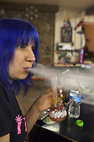 USA. Colorado state. Denver. Dabbing in iBAKE Denver, the first private membership head-shop that people can smoke marijuana in. A woman with blue hair is dabbing which is a slang term used to describe taking single dose hash hits of concentrates that are referred to as oil, erl, earwax, wax, budder, BHO or shatter using pipes and bongs that are made specifically for smoking these cannabis extracts. The pieces are designed to have a skillet or nail that made from glass, quartz or titanium that is heated with a handheld torch, the user then 'dabs' a small of the extract onto the hot nail causing the concentrate to flash into a vapor that you inhale. Dabbing is the street name for use concentrated butane hash oil, which has THC concentrations as high as 75% (allegedly reaching the 90+ range in some cases) compared with typical pot concentration of about 10 to 15 percent. Depending on the concentrate one long, hard hit can feel as having five blunts at once. The result is a rapid and very strong high. Cannabis, commonly known as marijuana, is a preparation of the Cannabis plant intended for use as a psychoactive drug and as medicine. Pharmacologically, the principal psychoactive constituent of cannabis is tetrahydrocannabinol (THC); it is one of 483 known compounds in the plant, including at least 84 other cannabinoids, such as cannabidiol (CBD), cannabinol (CBN), tetrahydrocannabivarin (THCV), and cannabigerol (CBG). 18.12.2014 © 2014 Didier Ruef