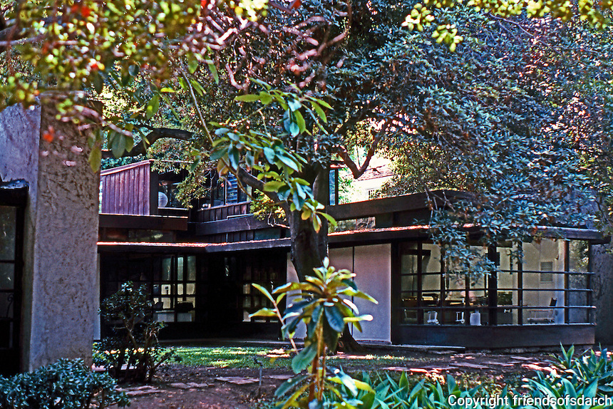 """Rudolph Schindler: Schindler House. Schindler wing from rear gardens. To the left, the fireplace of outdoor """"living room""""."""