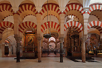 The hypostyle prayer hall, area built in the 10th century under Al-Hakam II, 961-976, with cathedral altars and behind, the area built under Al-Mansur, 987-988, in the Cathedral-Great Mosque of Cordoba, in Cordoba, Andalusia, Southern Spain. The hall is filled with rows of columns topped with double arches of a horseshoe arch topped by a Roman arch, in stripes of red brick and white stone. The first church built here by the Visigoths in the 7th century was split in half by the Moors, becoming half church, half mosque. In 784, the Great Mosque of Cordoba was begun in its place and developed over 200 years, but in 1236 it was converted into a catholic church, with a Renaissance cathedral nave built in the 16th century. The historic centre of Cordoba is listed as a UNESCO World Heritage Site. Picture by Manuel Cohen