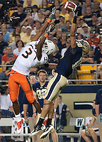 Pitt defensive back Jarred Holley (18) makes a spectacular interception over the outstretched arms of Miami wide receiver Travis Benjamin. The Miami Hurricanes defeated the Pittsburgh Panthers 31-3 at Heinz Field, Pittsburgh, Pennsylvania on September 23, 2010.