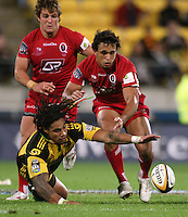 Ma'a Nonu tries to snare loose ball under pressure from reds flanker Andrew Shaw and centre Will Chambers during the Super 14 rugby match between Hurricanes and Reds at Westpac Stadium, Wellington, New Zealand on Friday, 7 May 2010. Photo: Dave Lintott / lintottphoto.co.nz