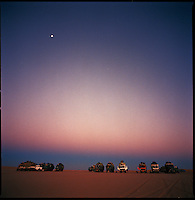 Sahara desert, Libya-Chad, November/December 2004..Every week, a convoy of 40 privately owned Libyan trucks loaded by the WFP with about 1000 metric tons of western food aid cross 2500 km of deep desert across Libya and Chad to reach more than 200 000 refugees from Darfur in camps near the Sudanese border. Drivers sleep in the truck cabins, mechanics on the desert ground; night temperatures can be freezing cold.