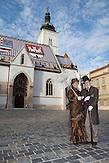 Ein Pärchen in der Kleidung des 19. Jahrhunderts spaziert durch die Altstadt vor der Markuskirche. / A couple in clothes of 19 Century walking through the old town before the St. Mark's Church.