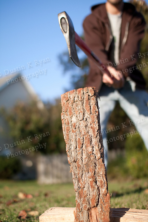 Man chopping and splitting wood with an axe shallow depth of field