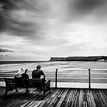 A couple sit on a bench and look out towards the beach and cliffs beyond