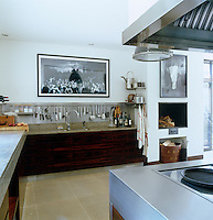 The wood veneer and stainless steel kitchen is by Bulthaup and the room is decorated with contemporary photographs from the owner's art collection