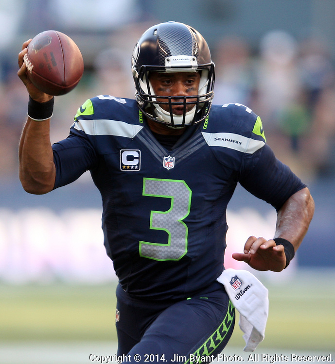 Seattle Seahawks quarterback Russell Wilson (3) looks to pass against the Denver Broncos during overtime at CenturyLink Field in Seattle, Washington on September 21, 2014.  Wilson completed 24 of 34 passes for 258 yards, two touchdowns and one interception in the 26-20 overtime win against the Broncos.  ©2014. Jim Bryant Photo. All rights Reserved.