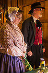 Old Bethpage, New York, USA. December 26, 2014. Wife SHERRI GUTHRIE and husband CHART GUTHRIE, dressed in traditional 19th Century clothing, visit the Salce imported Italian olive oil booth inside the Barn, at night, on the historic, rustic grounds of Old Bethpage Village Restoration, transformed by candlelight and Christmas decorations into a Nineteenth Century holiday experience for Long Island visitors. Candlelight Evenings are held until December 30th.
