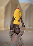 A displaced girl carries home a bottle of cooking oil from a United Nations-sponsored food distribution in Agok, a town in the contested Abyei region where tens of thousands of people fled in 2011 after an attack by soldiers and militias from the northern Republic of Sudan on most parts of Abyei. Although the 2005 Comprehensive Peace Agreement called for residents of Abyei--which sits on the border between Sudan and South Sudan--to hold a referendum on whether they wanted to align with the north or the newly independent South Sudan, the government in Khartoum and northern-backed Misseriya nomads, excluded from voting as they only live part of the year in Abyei, blocked the vote and attacked the majority Dinka Ngok population. The African Union has proposed a new peace plan, including a referendum to be held in October 2013, but it has been rejected by the Misseriya and Khartoum. The Catholic parish of Abyei, with support from Caritas South Sudan and other international church partners, has maintained its pastoral presence among the displaced and assisted them with food, shelter, and other relief supplies.