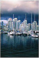 Boats huddled in marina on the North shore of False Creek with condominium towers of Yaletown in background, after a winter rain storm, Vancouver, BC.