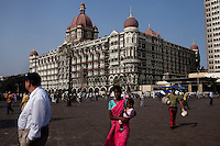 A beggar begs as tourists stand around the Taj hotel's old building that was attacked in the Mumbai 26/11 in year 2008 faces the Arabian sea on the Marine Drive in Mumbai, India. Photo by Suzanne Lee