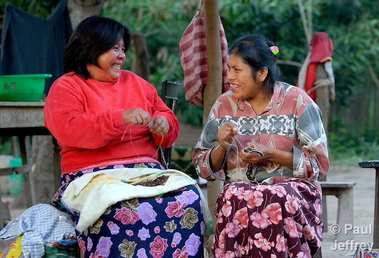 Marta Segundo (l) and Griselda Aria enjoy a light-hearted moment as they work together on artesan jewelry in Embarcacion, Argentina. Wichi indigenous women, they struggle to survive by crafting beautiful necklaces and other artwork, which is purchased from them for just a fraction of its value by intermediaries who take it to the large cities to sell at a huge markup.