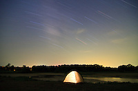 A lone illuminated tent camped at night in front of a lake with star trails overhead at Hubbard City Lakes in Hubbard, Texas, USA.