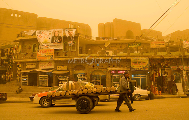 ERBIL, IRAQ: A man pulls his handcart through a heavy sandstorm in the Erbil market...The first sandstorm of the season hits northern Iraq...Photo by Metrography