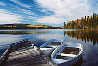 Empty Rowboats tied to Dock in Lake, Cariboo Region of BC, British Columbia, Canada