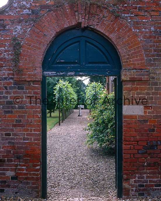 A door in the garden wall opens to a gravel path lined with pleached lime trees