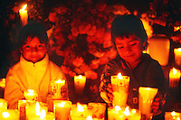 Children surrounded by candles and flowers, Night of the Dead (Noche de Muertos), November 1, Tzintzuntzan Cemetery, near Patzcuaro, Michoacan, Mexico