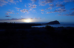 Sun rise in the Canarian waters, to the right is the rock known as red mountain, El Medano, Tenerife, Canary Islands.