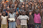 Children wave their hands as they line up before class in a school in the Ajuong Thok Refugee Camp in South Sudan. Situated in northern Unity State, the camp hosts thousands of refugees from the Nuba Mountains, located across the nearby border with Sudan. The Lutheran World Federation, a member of the ACT Alliance, provides a variety of services in the camp, including support for children's education.