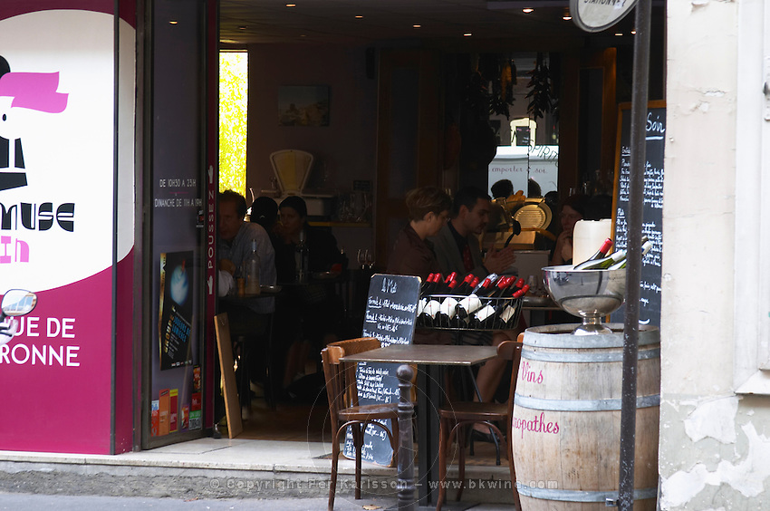 A cafe restaurant and wine shop in Paris, La Muse Vin Cave and Bistro, with a chair and table on the side walk and bottles on display. People sitting inside eating lunch