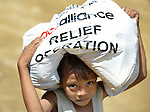 A small boy carries a bag of food and other relief supplies home following a distribution of the material to survivors in Estancia, a village in the Philippines that was hit hard by Typhoon Haiyan in November 2013. The storm was known locally as Yolanda. The food items were provided by the National Council of Churches of the Philippines, a member of the ACT Alliance.