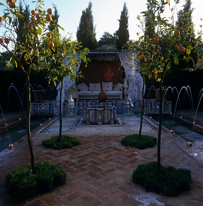At one end of the water garden is a raised banquette shaded by floating curtains overlooking a brick pathway planted with orange trees