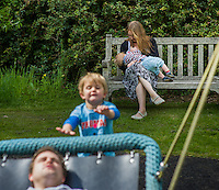 A mother  breastfeeding her child during a family outing to a local park and gardens. Her older boy is pushing her husband on a swing.<br /> <br /> 11-06-2015<br /> Hampshire, England, UK<br /> <br /> &copy; Paul Carter / wdiip.co.uk