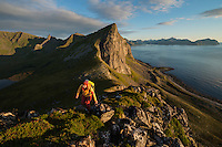 Female hiker ascending ridge near summit of Hornet mountain peak, Flakstadøy, Lofoten Islands, Norway
