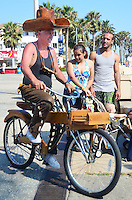 Wood Sculptor Rick Lawson rides his wooden bicycle while wearing his wooden cowboy hat at Ocean Front Walk on Monday, July 2, 2012.