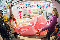 Owner Tabatha Lozano, left and NYC Council Speaker Melissa Mark-Viverito, right,  unveil the Sprinkle Splash Sweet Shoppe, the newest addition to the shops located in La Marqueta in East Harlem in New York, seen on its opening day, Saturday, April 2, 2016. Besides the incubator kitchen in the building there are a number of retail spaces in the revitalized facility rented by the entrepreneurs and small businesses which use the kitchen. (© Richard B. Levine)