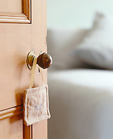 A fabric door handle hanger embroidered with the word 'hush'