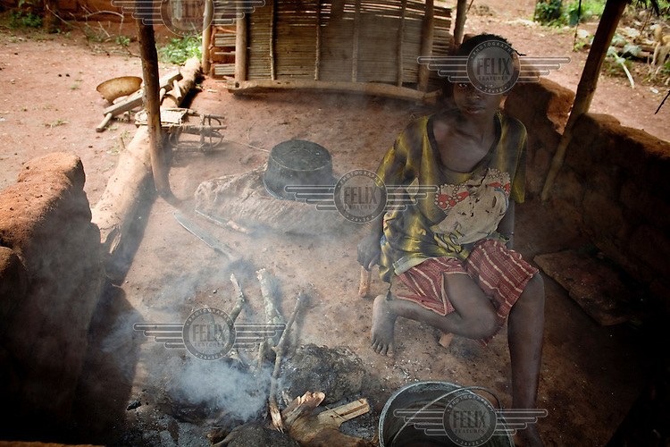 A woman prepares a meal next to a smoking fire in the Mbomou province.