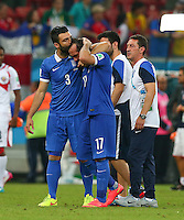 Theofanis Gekas of Greece is consoled by a team mate at full time after missing his penalty in the shootout