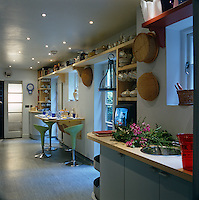 The long, narrow kitchen has versatile storage with high shelves for crockery and plates