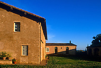 The buildings of this Tuscan country house surround a lawn sprinkled with small flowers