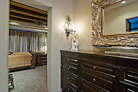 Beautiful dark wood dresser and ornate mirror is seen outside bedroom