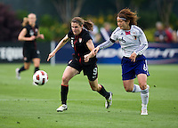 Heather O'Reilly (9) of the USWNT passes the ball away from Mizuho Sakaguchi (6) of Japan during the game at WakeMed Soccer Park in Cary, NC.   The USWNT defeated Japan, 2-0.