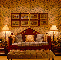 In this bedroom a series of oriental prints hangs above an ornate antique sofa whilst the room is suffused with golden light from two adjacent table lamps