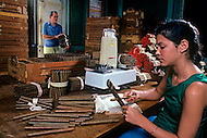Cuba, March 1992: After finishing rolling each cigar is taken out of the bundle and passed through a hole to control the ring size in order to have uniform size and to be ready for boxing, in La Corona, the largest cigar factory in Havana.